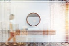 White bathroom interior, sink and mirror, woman. Woman walking near white sink standing on wooden countertop in bathroom with white walls, wooden floor and round royalty free stock image