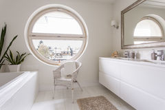 White bathroom with large round window Royalty Free Stock Photos