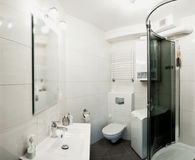 Bathroom interior design. White bathroom and shower with curved sliding door royalty free stock image