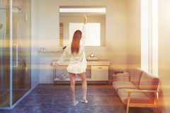 White bathroom with shower and sink, woman. Woman in a comfortable bathroom interior with white walls, a wooden shower with a glass door, a sink and a gray sofa stock photography