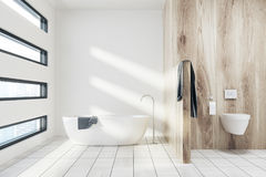White bathroom with a tub, toilet. White bathroom interior with a white tub, a towel hanging on it, a wooden wall fragment and a toilet. 3d rendering mock up vector illustration