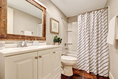 White Bathroom with vanity cabinet and wooden framed mirror. Stock Images