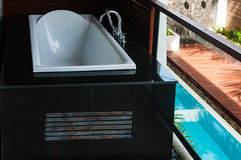 White bathtub at the balcony with pool view below Royalty Free Stock Images