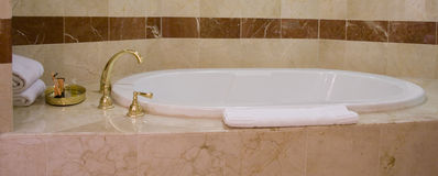 White bathtub and brass taps Royalty Free Stock Images