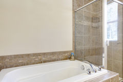 White bathtub with glass shower in the bathroom. Northwest, USA Stock Image