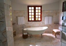 White Bathtub on White Tile Bathroom Near Brown Framed Clear Glass Window Stock Photos