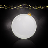 White bauble and decoration over black Royalty Free Stock Photo