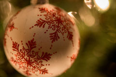 White bauble with red snowflakes. A close-up shot of a white bauble decorated with red snowflakes Stock Photography