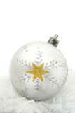 White bauble with star. White Christmas Bauble with gold star and snow Studio shot with copy space above Stock Photo