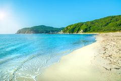White beach with blue sand, clear water rolls ashore. Royalty Free Stock Image