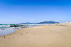 White beach, blue sky and clear sea. View down a white, sandy beach next to gently lapping waves of the crystal clear green sea. Blue sky and sun with people Stock Images