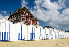 White beach cabins in a row on Franch coast. With a beautiful big old building above, France, Normandy Stock Photos
