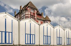 White beach cabins in a row on French coast. With a beautiful big old building above, France, Normandy Stock Photos