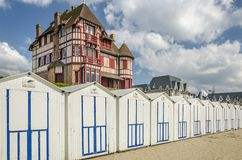 White beach cabins in a row on French coast. With a beautiful big old building above, France, Normandy Stock Photography
