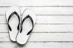White Beach flip flop on a white wooden floor stock images