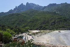 White beach between the foot of the mountains with a boat dock and azure sea. On the island of Corsica Stock Images