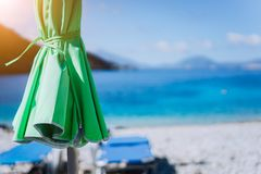 White beach with sunbeds and umbrella by clear turquoise blue waters of Mediterranean sea on sunny hot summer day royalty free stock photos