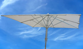 White beach umbrella concept over blue sky Stock Photo