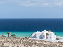 A white beach villa at turquoise ocean. Royalty Free Stock Photo