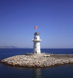 White beacon near coast with a red flag Stock Image