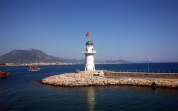 White beacon near coast with a red flag Stock Photo