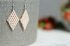 White beaded earrings on a gray background Stock Photo