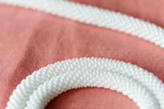 White beaded necklace on a textile background coral color. Close up royalty free stock images