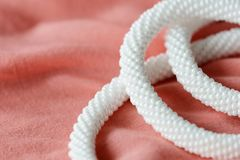 White beaded necklace on a textile background coral color. Close up royalty free stock photography