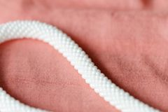 White beaded necklace on a textile background coral color. Close up royalty free stock image