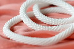 White beaded necklace on a textile background coral color. Close up stock photography