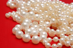 White beads on a red background. White beads on a red royalty free stock images