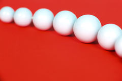 White beads on a red background Royalty Free Stock Photography