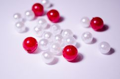 White beads. Beads are red. Separate beads. Placer beads. Beads are bigger and smaller. A handful of beads. Imitation pearls. Plastic beads. Placer beads stock photos