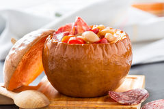 White bean and salami sausage stew in pumpkin bowls Royalty Free Stock Photo