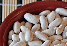 White beans. Macro view of white beans in a red bowl Royalty Free Stock Photography