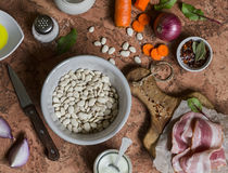 White beans, bacon, carrots, red onion, spices and herbs - ingredients for making bean mash with bacon. On a stone background. Stock Photo