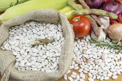 White beans in a bag with some vegetables. Ready for cooking Royalty Free Stock Photography