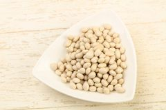 White beans. Dry white beans in the bowl over wooden background Royalty Free Stock Photos