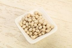 White beans. Dry white beans in the bowl over wooden background Stock Photography
