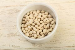 White beans. Dry white beans in the bowl over wooden background Stock Photos