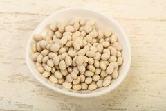 White beans. Dry white beans in the bowl over wooden background Royalty Free Stock Images