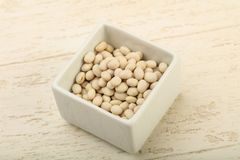 White beans. Dry white beans in the bowl over wooden background Royalty Free Stock Photo