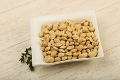 White beans. Raw White beans in the bowl over wooden background Royalty Free Stock Images