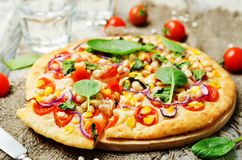 White beans, spinach, corn and tomato pizza with white beans cru. St. toning. selective focus Stock Photography