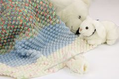 White bear and rabbit pluches sleeping under the homemade baby blanket. On white background stock photography