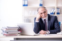 The white bearded old businessman employee unhappy with excessive work. White bearded old businessman employee unhappy with excessive work royalty free stock images