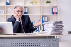 The white bearded old businessman employee unhappy with excessive work. White bearded old businessman employee unhappy with excessive work stock photography