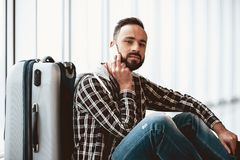 White bearded tired man sitting near suitcase stock images