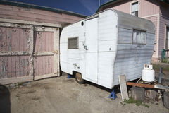 White beatup trailer parked in front of pink garage, Ventura, California, USA Stock Image