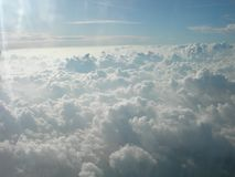 White beautiful clouds kissing the sun and the sky.Day light in the clouds. View from a plane window over puffy clouds Royalty Free Stock Photo
